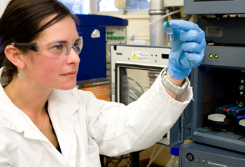 A female scientist in a labcoat and wearing safety glasses and gloves, looking closely at a vial