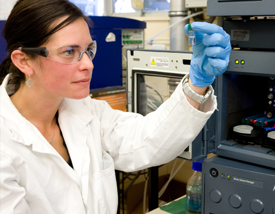 A female scientist in a labcoat and wearing safety glasses and gloves, looking closely at a vial.
