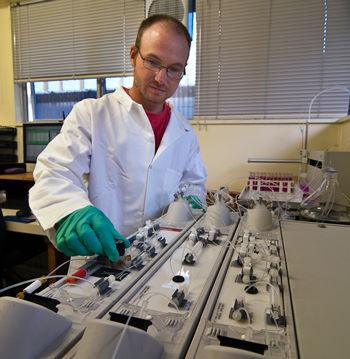 A male scientist operating an instrument.